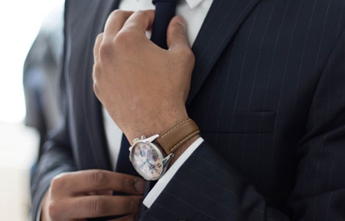 Business man wearing watch and tightening his tie